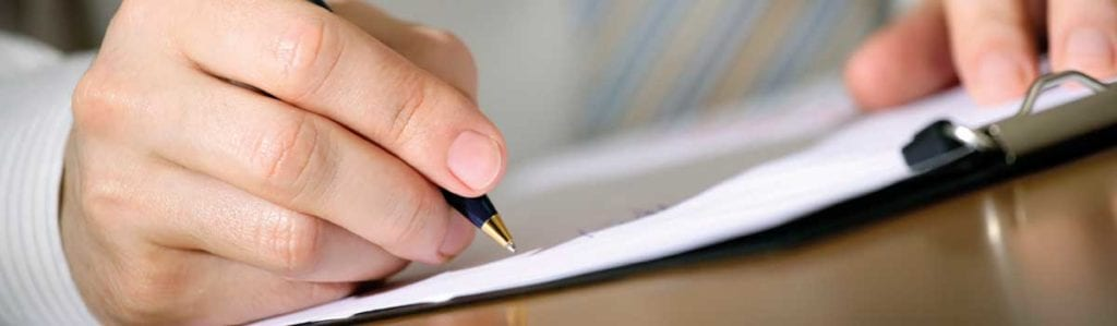 Close up of hand holding pen writing social care cover letter