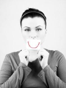 Sad woman with fake smile.