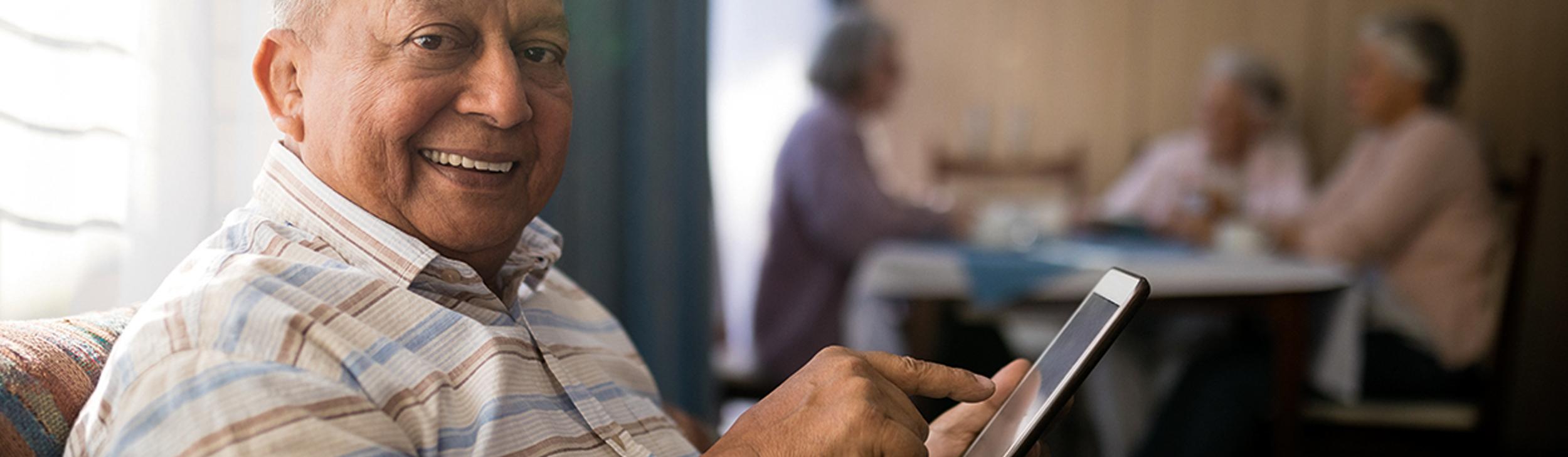 Older man on tablet smiles to camera